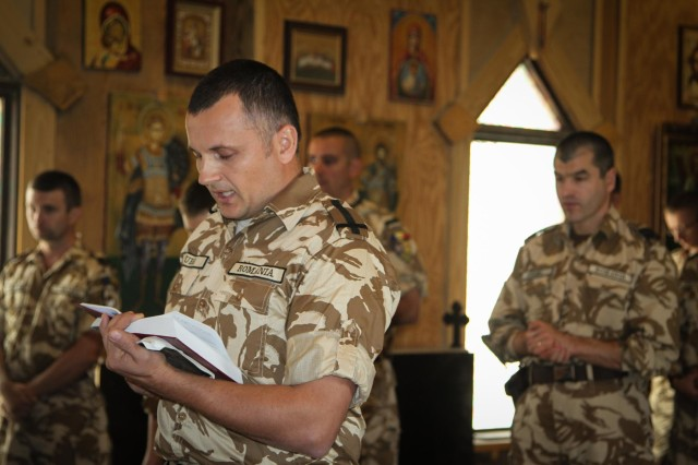 Maj. Daniel Puha, Romanian Public Affairs officer, National Support Element, participates in the Romanian Orthodox liturgy held at the St. Gheorghe Chapel on Kandahar Airfield, Afghanistan, Oct. 13, 2013. (U.S. Army photo by Cpl. Mariah Best)