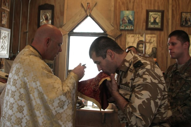 Maj. Ruston Hill, command chaplain for Combined Joint Special Operations Task Force - Afghanistan, gives the Holy Communion to Romanian soldiers during an Orthodox service held at St. Gheorghe Chapel on Kandahar Airfield, Afghanistan, Oct. 13, 2013. (U.S. Army photo by Cpl. Mariah Best)