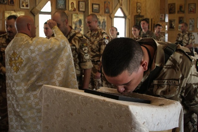 A Romanian soldier kisses an icon after being blessed with holy water during a Romanian Orthodox service held at St. Gheorghe Chapel on Kandahar Airfield, Afghanistan, Oct. 13, 2013. (U.S. Army photo by Cpl. Mariah Best)
