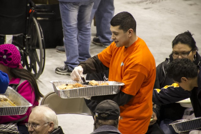 """Spc. Fernando Maldonado, 5th Squadron, 1st Cavalry Regiment, 1st Stryker Brigade Combat Team, 25th Infantry Division joined more than 60 Soldiers who assisted feeding the many guests who attended the Alaska Federation of Natives Convention at the Big Dipper Ice Arena Oct. 24. """"Being able to help out and experience an event like this and learn more about the Alaska Native culture meant a lot,"""" said Spc. David Freer, president, Fort Wainwright BOSS program."""