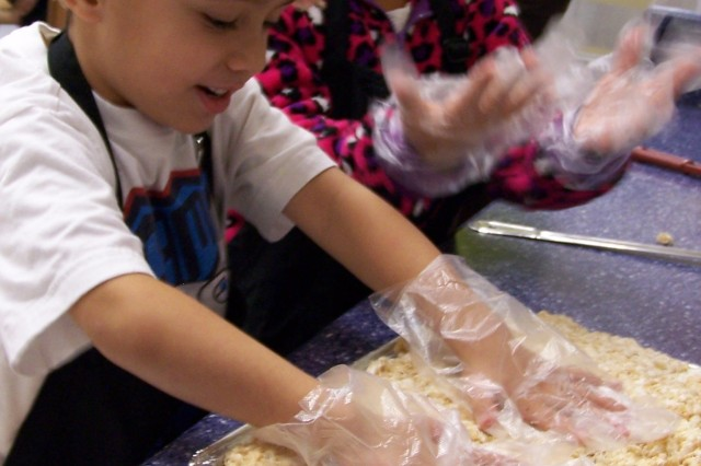Josiah and Victoria spread crispy rice cereal mixed with marshmallow in pans. Josiah is the son of Karen and Staff Sgt Boyden, 3-21st, 1-25th SBCT, and Victoria is the daughter of Nelson and Sgt. Eliana Ortiz, 1st Battalion, 52nd Aviation Regiment, USARAK Aviation Task Force.