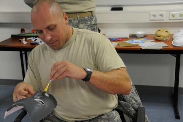 "Staff Sgt. Michael Czarnecki, Cadre, Warrior Transition Battalion, channels ""The Terminator"" as he paints a mask tough enough to motivate a hard workout."