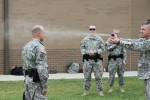 SSG Wallis is spraying SGT Payne with OC