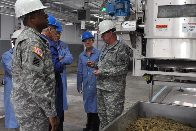 KINGSPORT, Tenn. - (Left to Right) Colonel David Musgrave, commander of Pine Bluff Arsenal, and Brigadier General John McGuiness, Program Executive Officer for Ammunition and Senior Commander of Picatinny Arsenal, inspect the peanut-brittle-like end product on the Comp B melt-cast line at Holston Army Ammunition Plant during the April 2013 plant tour.