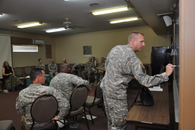 Capt. Bradley Walgren, a chaplain assigned to the 158th Maneuver Enhancement Brigade with the Arizona Army National Guard, writes on a white board during a chaplains' spiritual training session at the Franciscan Renewal Center in Scottsdale, Ariz.