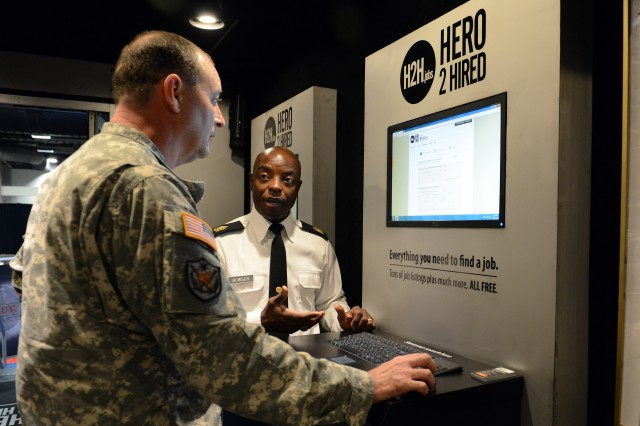 Sgt. Maj. Wayne Bowser Sr., the senior enlisted adviser for Family and Employer Programs and Policy in the Pentagon's Office of Reserve Affairs, discusses resources available on H2H.jobs, during a visit by an officer to the Hero 2 Hired Mobile Job Store, Washington, D.C., Oct. 23, 2013.