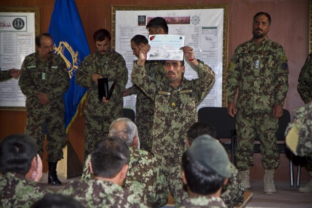 Afghan National Army Sgt. Saidullah with the Signal Khandak, 203rd Corps, proudly displays his Certificate of Achievement for the audience, during an awards ceremony Oct. 30, 2013, for the Signal Olympics held at Forward Operating Base Thunder, Afghanistan.