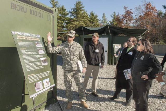 "Lt. Col. Ross Poppenberger, Product Manager Force Sustainment Systems (left), speaks with Katherine Hammack, assistant secretary of the Army for Installations, Energy and Environment, about energy-efficient Rigid Wall Camps, during the Nov. 5, 2013, ""Base Camp Resource and Energy Efficiency Day"" at the Army Base Camp Integration Laboratory, Fort Devens, Mass."