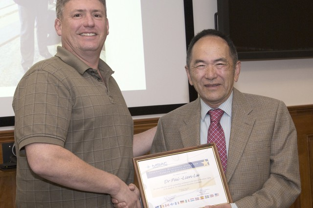 Ernest L. Baker, Picatinny's senior research scientist for insensitive munitions, congratulates Pai-Lien Lu for his selection for the Munitions Safety Award from the North Atlantic Treaty Organization.
