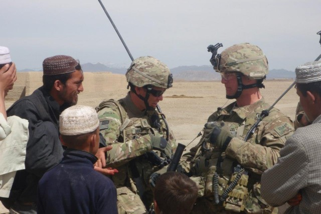 Sgt. 1st Class Scott Cormack (right) and Staff Sgt. David Doughty interact with locals in the Bandeh Sardeh district, Afghanistan, in March 2011. Today, Cormack serves as the Warrior Transition Unit platoon sergeant at Walter Reed Military Medical Center, Md., overseeing 30 seriously wounded, ill or injured Soldiers.