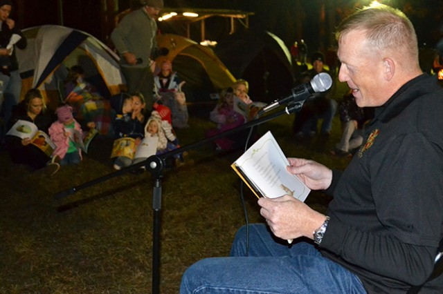 Col. Stuart J. McRae, garrison commander, reads a story to children at the Camping Under the Stars event at Lake Tholocco's West Beach last year.