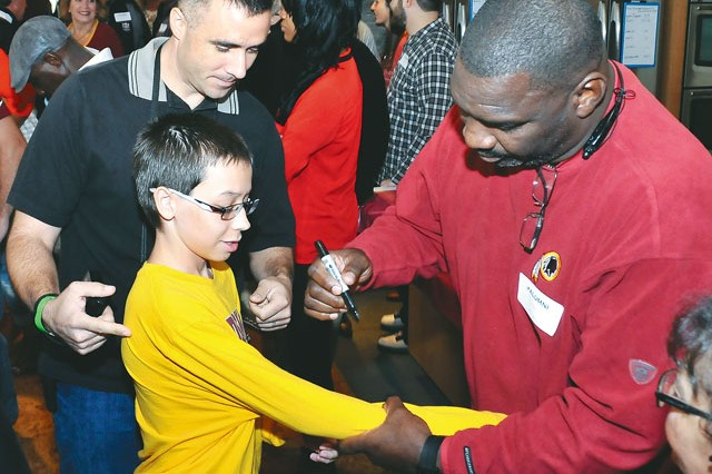 Doug Williams, former Washington Redskins quarterback, right, signs CJ Oakley's shirt during the Washington Redskins Homecoming Military Meet 'n' Greet at the Fort Belvoir USO Warrior and Family Center, Saturday.