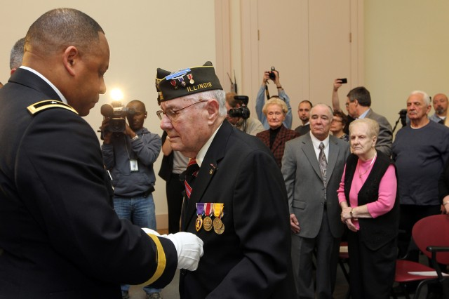 Brig. Gen. Gracus K. Dunn, commanding general of the 85th Support Command and deputy commanding general for Support of First Army Division West, pins six medals, to include the Purple Heart, on World War II veteran, Frank Andrews, Nov. 3, during a surprise ceremony at the First Division Museum at Cantigny Park in Wheaton, Ill.