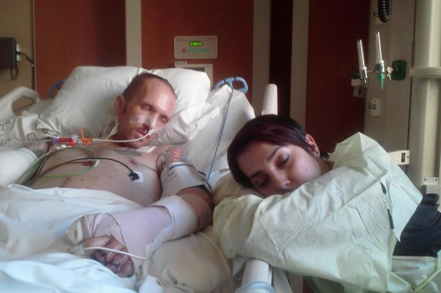 Capt. Edward Klein, a triple amputee, was wounded in Afghanistan, October 22, 2012. Pictured here, his wife Jessica catches some sleep while he recovers at Walter Reed National Military Medical Center.