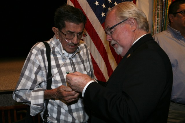 Congressman Ron Barber, Arizona District 2, explains the details of the Army Commendation Medal with Valor Device to Retired Staff Sgt. Alejandro Gonzales who received the medal on Fort Huachuca Wednesday in honor of an act of heroism Gonzales performed in Vietnam 46 years earlier.
