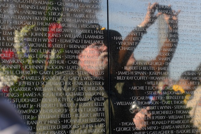 The reflection of a Vietnam veteran is seen at the Vietnam Veterans Memorial Wall, Washington, D.C., Nov. 11, 2013.