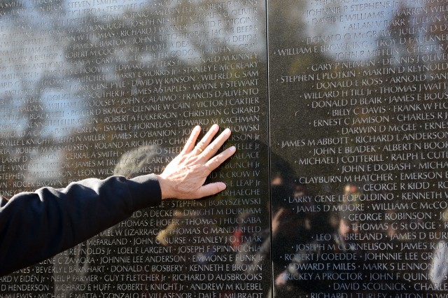 A visitor to the Vietnam Veterans Memorial pauses at the wall in remembrance of the fallen, Washington, D.C., Nov. 11. 2013.