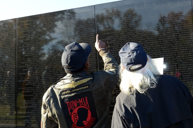 A Vietnam veteran points to a name on the Vietnam Veterans Memorial Wall in Washington, D.C., Nov. 11, 2013.
