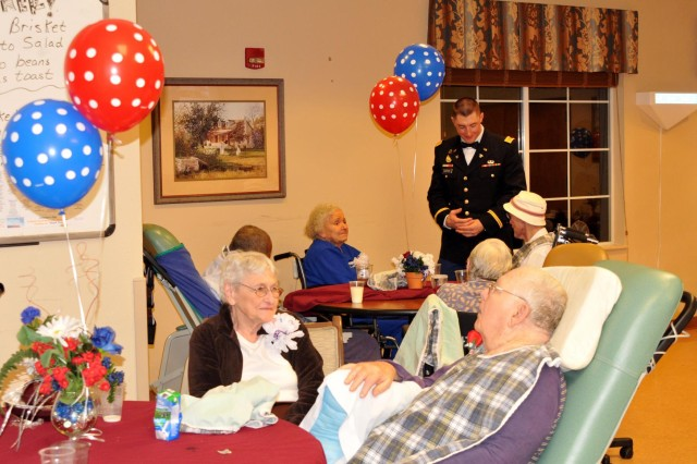 A young officer chats with residents at the William R. Courtney Texas State Veterans Home in Temple, Texas, during a Veterans Day Ball on Nov. 11. Several soldiers spent the morning assisting the center to commemorate Veterans Day with a ceremony, and mixed and migled with the residents during the evening formal event, which followed the usual protocol of having a receiving line, posting the colors, invocation, guest speaker, retiring the colors and even some music allowing the more mobile residents to dance once the dance floor opened.