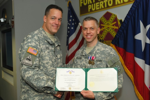 Col. Tom Byrd, the commander of the 3rd Military police Group (CID), U.S. Army Criminal Investigation Command, presents the Soldier's Medal to Special Agent James Spalding, a CID special agent with the Puerto Rico CID Office, November 4, 2013. Spalding was awarded the medal for saving the lives of two Canadian citizens from drowning at Flamenco Beach in Culebra, Puerto Rico.