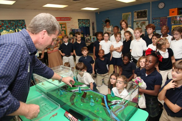 Regulatory Spc. Brian Moore uses an interactive floodplain model to demonstrate how wetlands absorb storm water and filter drinking water to a class of third grade students at Marshpoint Elementary School, Nov. 5, 2013. (USACE photo by George Jumara)