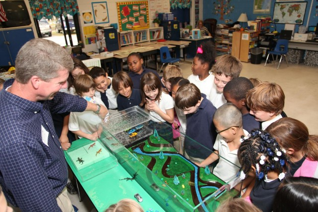 Regulatory Spc. Brian Moore uses an interactive floodplain model to demonstrate how wetlands absorb storm water and filter drinking water to a class of third grade students at Marshpoint Elementary School, Nov. 5, 2013. USACE photo by George Jumara.