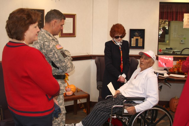 "Lt. Gen. David L. Mann, commanding general of U.S. Army Space and Missile Defense Command/Army Forces Strategic Command, and his wife, Robyn, speak with Army Staff Sgt. Theo Calvin and his wife, Virginia, on Veterans Day at the Floyd E. ""Tut"" Fann State Veterans Home. Calvin served in the 1st Infantry Division during World War II. He saw combat in North Africa, Sicily, France and Germany."