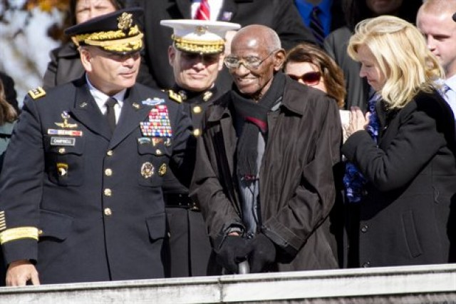 Richard Overton stands as President Barack Obama acknowledges him as America's oldest living World War II veteran, during the Veterans Day ceremony at Arlington National Cemetery, Va., Nov. 11, 2013. Army Vice Chief of Staff Gen. John F. Campbell joins Overton at the event.