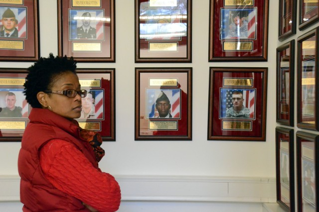 A visitor at the Remembrance Room during opening day looks at some of the 92 photos displayed on the walls. The room was created to honor Baumholder Soldiers who have lost their lives and their surviving family members.