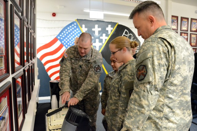 "Lt. Col. Mike Sullivan, U.S. Army Garrison Baumholder commander, enlists the assistance of Pfc. Veronica Cerros and Pfc. Tonya Waters in cutting the traditional ""event cake"" during opening day for the Remembrance Room.  Cerros and Waters are the artists that created the mural that is in the background. Also participating is Command Sgt. Major Ronald Creighton, USAG Baumholder command sergeant major."