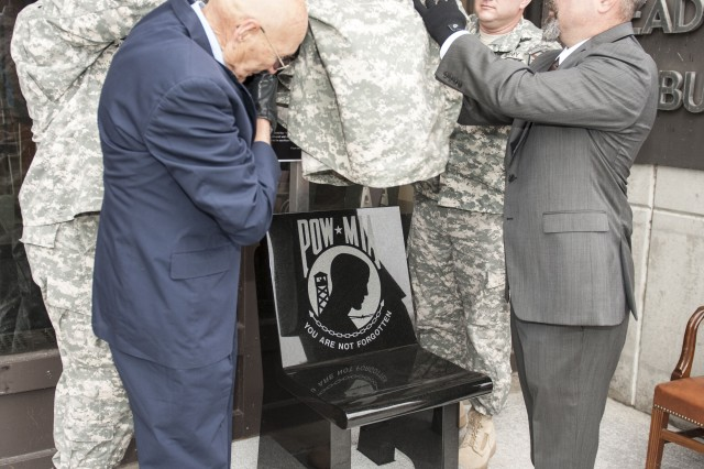 William Skipper, Command Sgt. Maj. Robert Beausoleil, Lt. Col. Brian Greata and Darren Bean unveil the new POW/MIA chair outside Building 1 Nov. 12. The chair is a standing memorial of all service members who were or still are prisoners of war and missing in action.