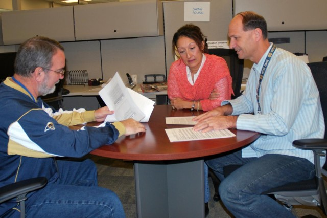 From left to right, Philip Sadler, Carole Dowling, and Rene Guionnaud Jr., from SDDC's Defense Transportation Coordination Operations Support Branch, review the progress of Defense Logistic Agency's First Destination Transportation Initiative, which began Oct. 28.