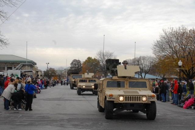 Vehicles of the 3rd Brigade Combat Team, 10th Mountain Division drive by the audience during the Veterans Day parade held at the New York State Fairgrounds in Syracuse, N.Y., Nov 9. The vehicles were later made a part of a static display, allowing the public to get a closer look at them.