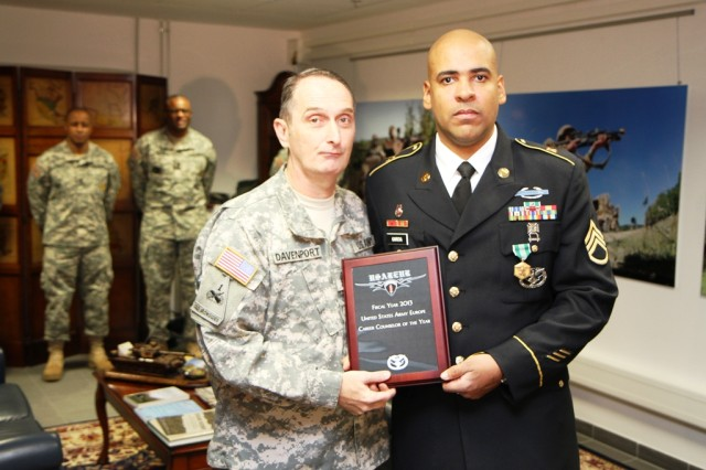 Staff Sgt. Efrain D. Garcia Jr. accepts a plaque naming him the 2013 U.S. Army Europe Career Counselor of Year from Command Sgt. Maj. David S. Davenport Sr., the USAREUR senior enlisted advisor, in Wiesbaden, Germany, Nov. 5.
