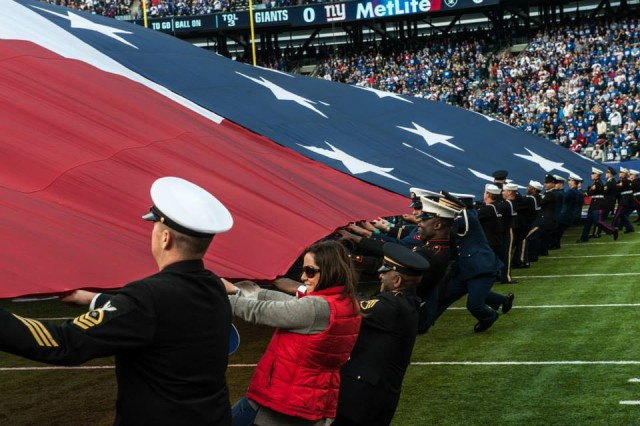 Servicemembers fight to pull an American Flag across the field before the start of the New York Giants vs. Oakland Raiders game at the MetLife Stadium, East Rutherford, NJ on November 10, 2013 (U.S. Army Photo by Sgt. Mikki L. Sprenkle/Released) Digital