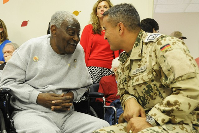 Jesse Stanford, army veteran, sits and talks with Sgt. Major Mohammad Bouhloui, Fort Rucker German army liaison staff, about his tour in Germany after WWII Nov. 11 at the Henry Country Health and Rehabilitation Center in honor of Veteran's Day.