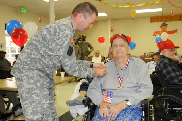 Mac Oates, Navy veteran, is pinned by Staff Sgt. Michael Mayo III, NCOA, Nov. 11 at the Henry Country Health and Rehabilitation Center in honor of Veteran's Day.