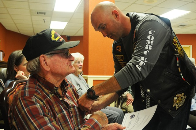 James Pouncey, Army veteran, is pinned by Sgt. First Class Shane Cook, 1st Battalion, 223rd Aviation Regiment and combat veterans motorcycle association public relations officer, Nov. 11 at Enterprise Health and Rehabilitation in honor of Veteran's Day.
