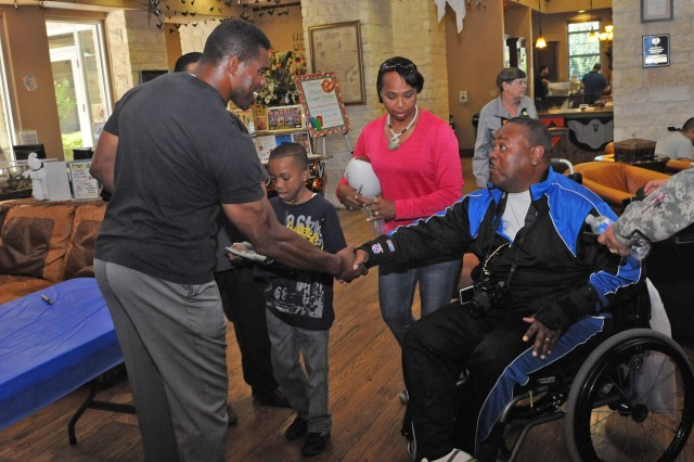FORT SAM HOUSTON, Texas - Retired Master Sgt. Mack Cole Jr. (right), shakes hands with one of his biggest heroes, Herschel Walker, during Walker's visit with wounded warriors and their families Oct. 24 at the Warrior and Family Support Center. Walker is a former college and pro-football athlete. Cole, a native of San Antonio, was accompanied by his wife, Angie, and grandson, Amari, 12. Before retiring, Cole worked as an Army military policeman. Other celebrities meeting with Soldiers and family members were actors Peter Mayhew, Walter Jones, Glenn Morshower and David Yost.