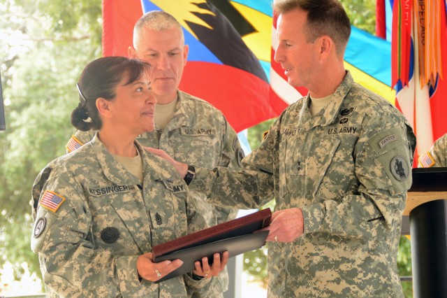"FORT SAM HOUSTON, Texas - Maj. Gen. Joseph DiSalvo and Command Sgt. Maj. Dennis Zavodsky present an award to Sgt. Maj. Linda Kessinger for her support during the Hispanic Heritage Month cultural reception Oct. 28. The event, sponsored by U.S. Army South, was held at the pavilion behind Building 1001. ""This observance promotes understanding of teamwork, harmony, pride and spirit among all groups "" not just one specific group,"" said Kessinger. ""It isn't only about celebrating culture; it focuses on the contributions Hispanics and Latinos have made to the country."" The theme for the celebration was ""Serving and Leading our Nation with Pride and Honor."" Kessinger is the senior enlisted leader for personnel at U.S. Army North (Fifth Army). Maj. Gen. Joseph DiSalvo is the commanding general of Army South and Command Sgt. Maj. Dennis Zavodsky is his senior enlisted leader."