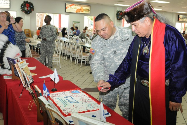 "FORT SAM HOUSTON, Texas - Sgt. 1st Class Adam Mayo joins Erwin DeLuna in cutting a cake during the National American Indian Heritage Month kickoff Oct. 31 at the Fort Sam Houston Post Exchange. This year's theme is ""Guiding Our Destiny with Heritage and Traditions."" The U.S. Army North (Fifth Army)-sponsored event was the official start to the historical month at Fort Sam Houston. Mayo is the program manager and equal opportunity advisor for Army North. DeLuna is the president of the United San Antonio Pow Wow Inc."