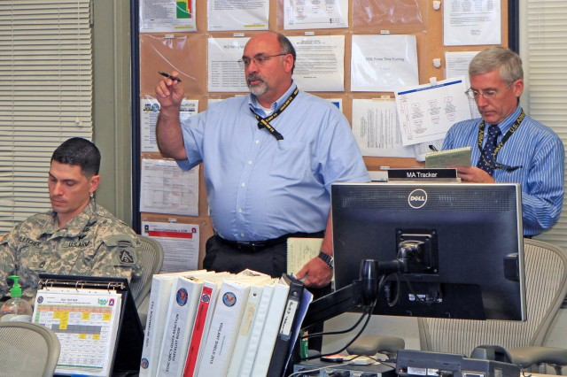FORT SAM HOUSTON, Texas - Daryl Kinman (center), poses a question as Roger Bass listens and scribes notes during their preview of the commander's update brief slides Oct. 30 as they prepare for the actual briefing. The CUB is intended to bring the commanding general, U.S. Army North (Fifth Army), or his representative, up to speed on new developments taking place during the exercise. Kinman serves as the deputy, Army North training section; Bass serves as the chief of land operations, Army North.