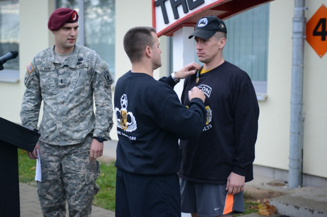 Lt. Col. Kyle Reed, commander of the 1st Squadron (Airborne), 91st Cavalry Regiment, pins an award on the individual winner , Capt. Adam Green, from the Joint Multinational Readiness Center in Hohenfels, Germany.