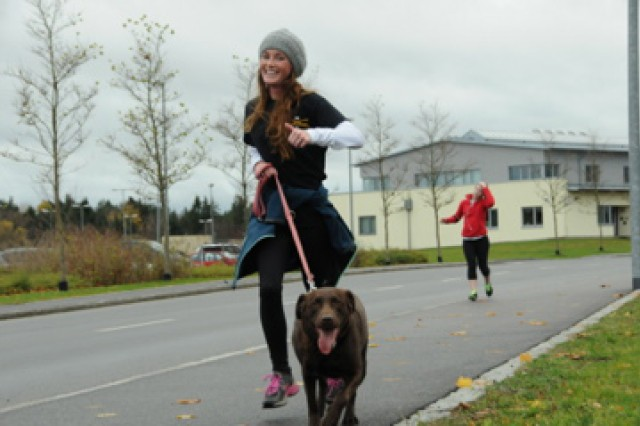 Sarah Chambers and her cohort, Sadie, show their Cav. pride at the Running of the Herd at Grafenwoehr, Germany, Nov. 7.