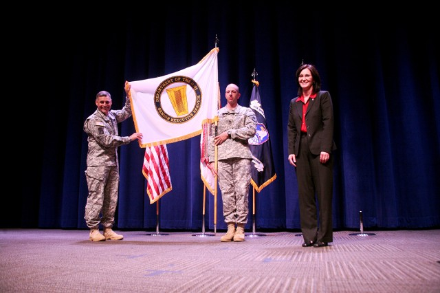Lt. Gen. David L. Mann, commanding general, U.S. Army Space and Missile Defense Command/Army Forces Strategic Command, left, presents the Senior Executive Service flag to Julie W. Schumacher, the new director for SMDC's Technical Center, during a ceremony Nov. 12 at the Von Braun III auditorium. Staff Sgt. John Schaefer is holding the flag.