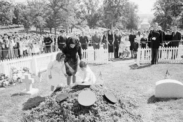 Caroline, Jacqueline, and John F. Kennedy, Jr., place flowers at the base of the eternal flame.
