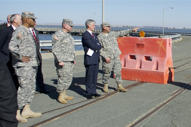 Secretary of the Army John McHugh (second from the right) discusses Military Ocean Terminal Concord, known as MOTCO, infrastructure improvements with Maj. Gen. Thomas Richardson (third from the right) and Lt. Col. Kenneth Sheets (far right), during a visit to MOTCO, Calif., Nov. 15, 2015.  Richardson is commanding general, Military Surface Deployment and Distribution Command, and Sheets is commander of SDDC's 834th Transportation Battalion at MOTCO.  Also on hand during the briefing were Brig. Gen. David Turner, commander, U.S. Army Corps of Engineers South Pacific Division; and Bruce Busler, who is dual-hatted as director, U.S. Transportation Command Joint Distribution Process Analysis Center, and executive director of SDDC's Transportation Engineering Agency.