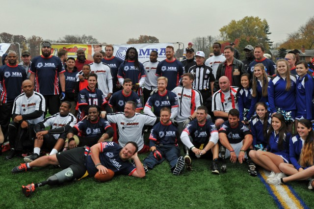 All in a day's fun, the Wounded Warrior Amputee Football Team mixes with the NFL and Washington Redskins Alumni and Bishop O'Connell High School cheerleaders at the Flag Football Challenge in Arlington, Va., Nov. 16, 2013, as part of Warrior Care Month. Sponsored by the non-profit Military Benefit Association, $60,000 was raised for the amputees. The gridiron battle outcome came down to the final seconds with the amputees winning 28-21.