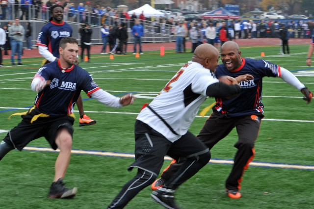 Former Redskin Brian Mitchell tries to move around former Cleveland Browns player Eric Metcalf as former Marine Tim Lang rushes in to yank the flag off Mitchell. The Wounded Warrior Amputee Football Team went up against the Washington Redskins Alumni & NFL Alumni in a Flag Football Challenge at Bishop O'Connell High School in Arlington, Va., Nov. 16, 2013, as part of Warrior Care Month. Sponsored by the non-profit Military Benefit Association, $60,000 was raised for the amputees. While the gridiron battle's outcome came down to the final seconds, the amputees won out 28-21.