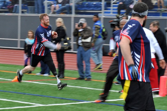 Former Sailor Robert Donnelly rushes along the sideline for the Wounded Warrior Amputees Football Team, which took on the NFL and Washington Redskins Alumni Flag Football Challenge at Bishop O'Connell High School in Arlington, Va., Nov. 16, 2013, as part of Warrior Care Month. Sponsored by the non-profit Military Benefit Association, $60,000 was raised for the Amputees. The gridiron  battle's outcome came down to the final seconds with the Amputees winning 28-21.